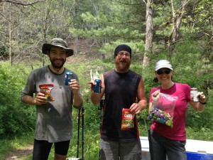 Three happy hikers at a freshly filled Trail Magic box
