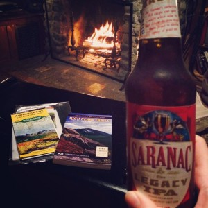 December 26, 2015: Sitting fireside with my Adirondack guidebook and map while I sip upon my Adirondack beer.