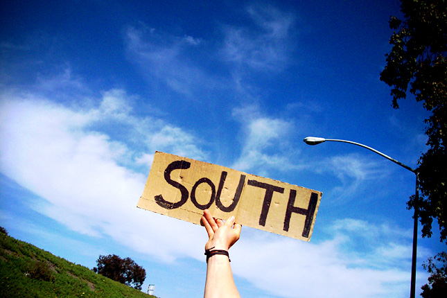 "Hand holding a sign saying ""South"" in front of a blue sky"