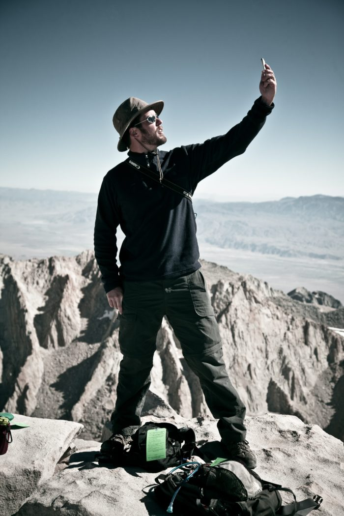 Person in a hat on a mountain top holding their cell phone up into the sky