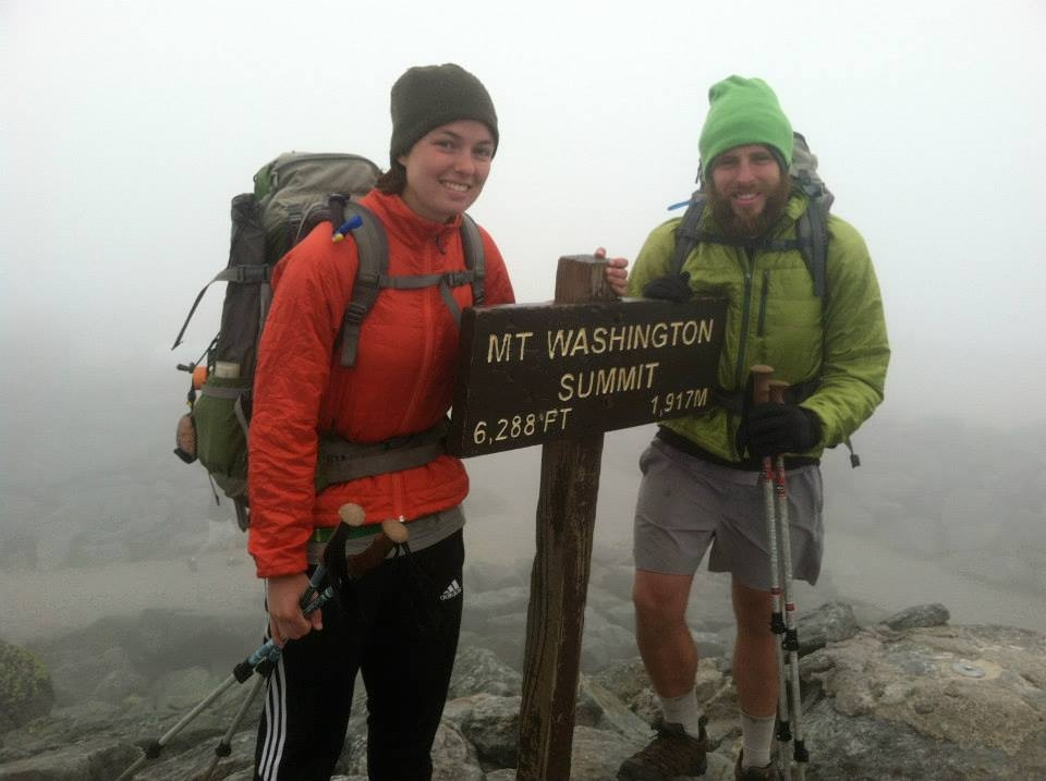 a photo of a couple at the summit of Mt. Washington, New Hampshire during a thru hike