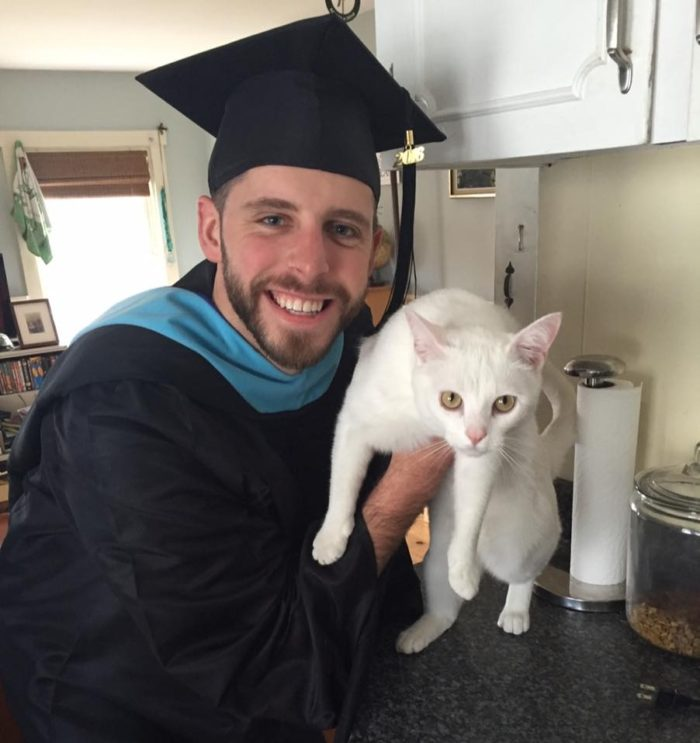 photo of a graduate with a white cat
