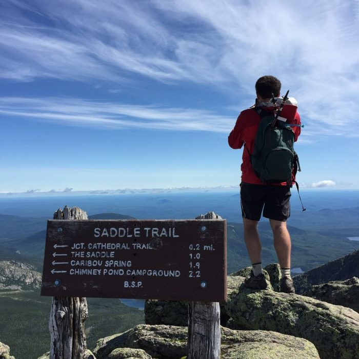 a photo of a man hiking in Maine