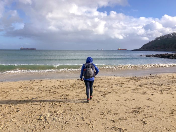 Gail looks out to sea on the beach wearing hiking kit and carrying a full back pack.