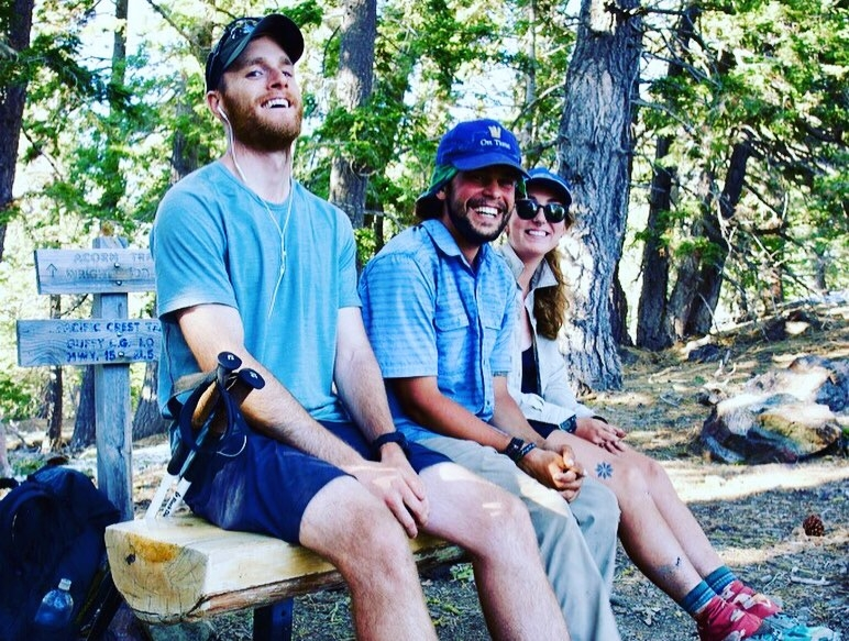Three hikers sitting on a bench at a campsite on the mountain.