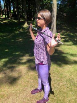 Holding trekking pole in front of shoulders