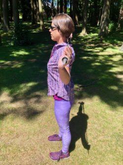Holding trekking pole behind shoulders