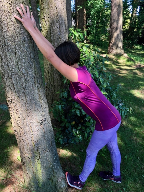 Shin stretch against a tree