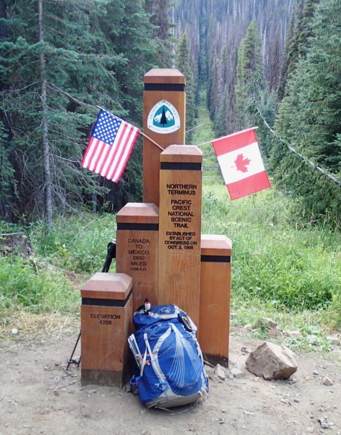 Wooden PCT monument with US and Canada flags