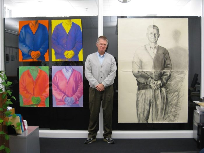 man in front of paintings