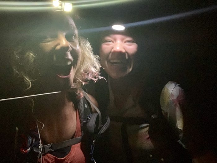 Two girls smiling and wearing head torches in the dark