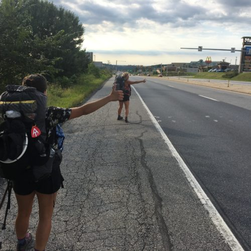 Two hikers hitching on a highway