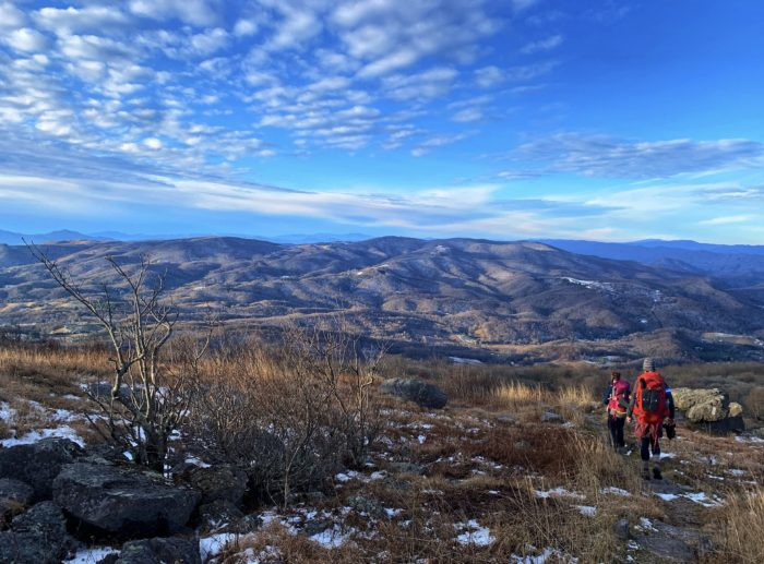 Blue sky and wide mountain range views in Roan Highlands with hikers descending