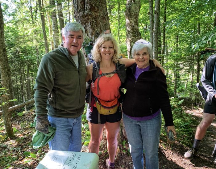 Hiker with her arms around two trail angels posing for picture in the woods next to a cooler.
