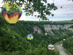 Hot air balloons hovering over a tree-lined gorge in Letchworth State Park, New York
