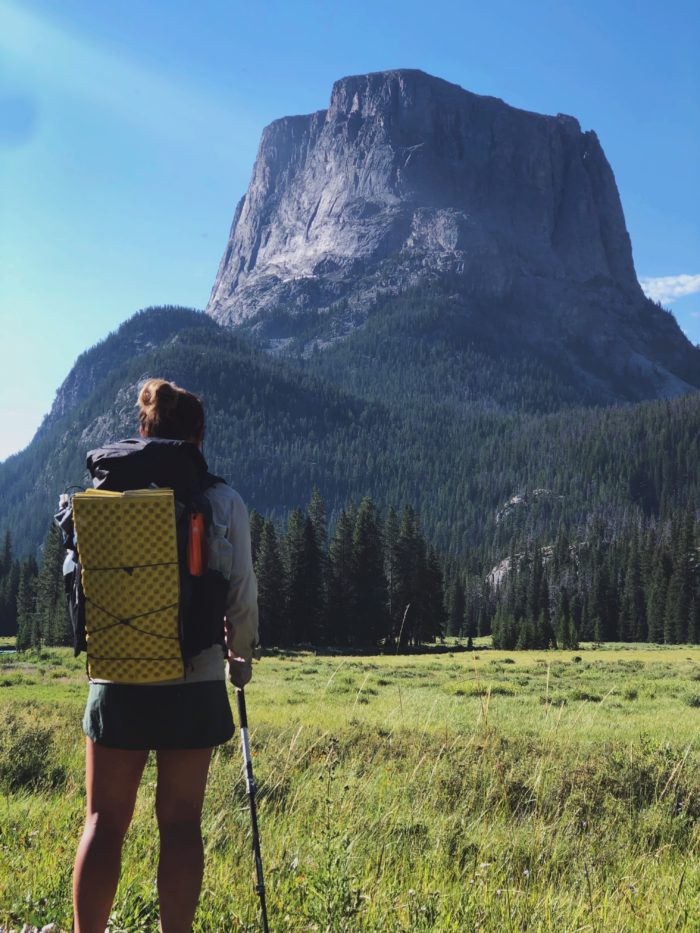 A woman standing in front of Flat Top Mountain with her back to the camera wearing a Superior Wilderness Designs Long Haul 40 pack.