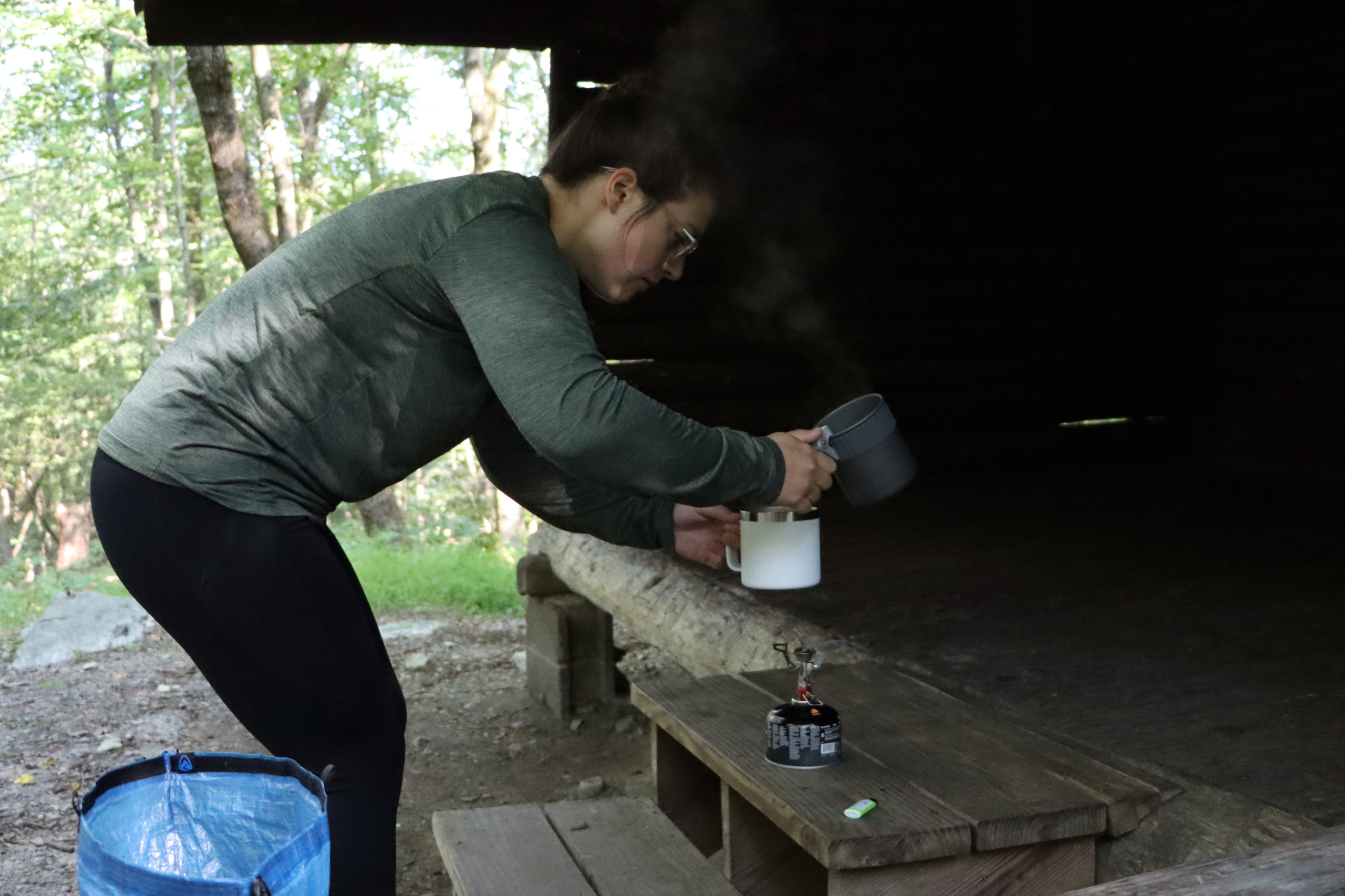 The blogger using an MSR Pocket Rocket stove to heat water in an MSR pot.