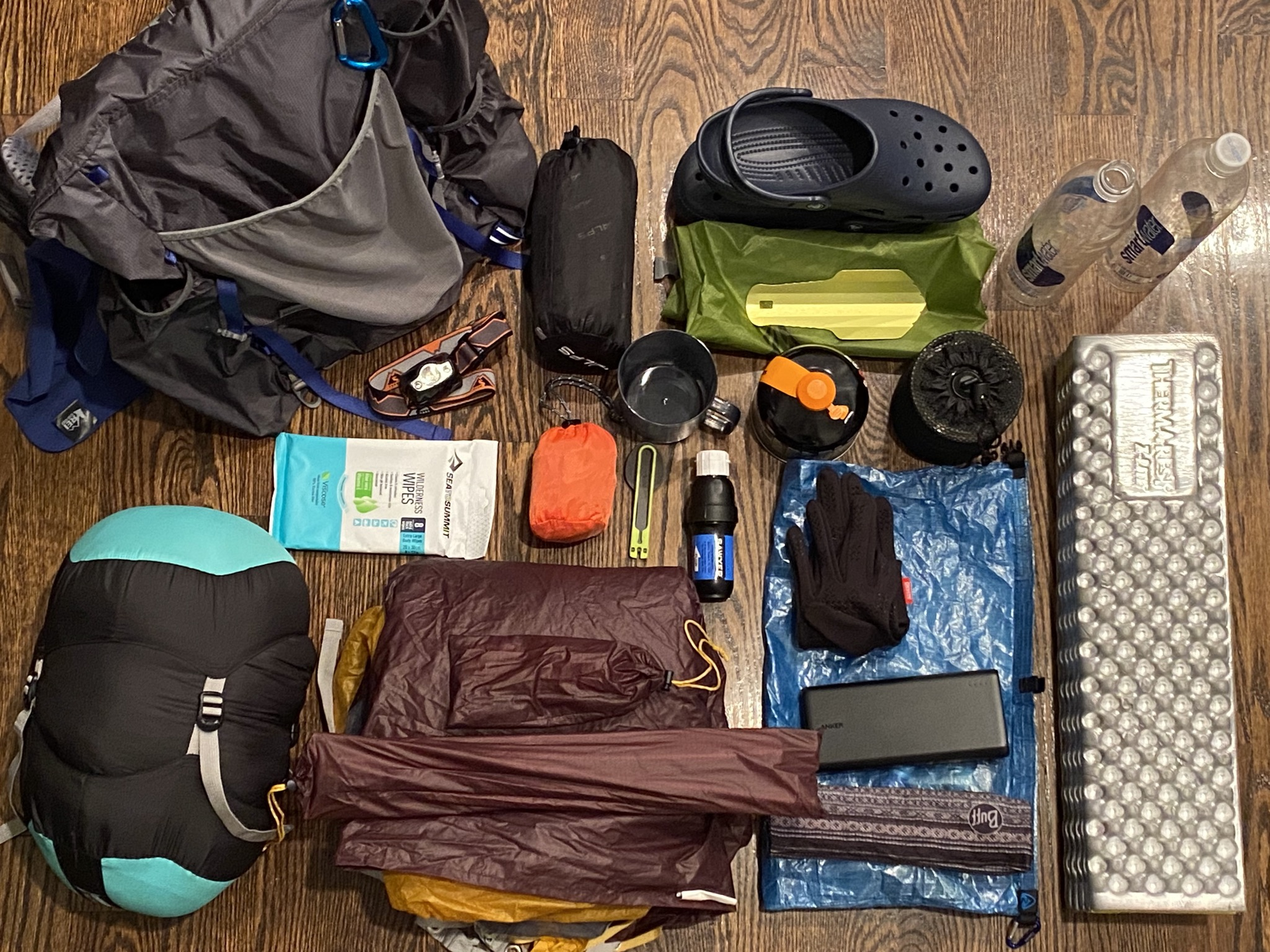 Backpacking gear, assorted, arranged on a wood floor.
