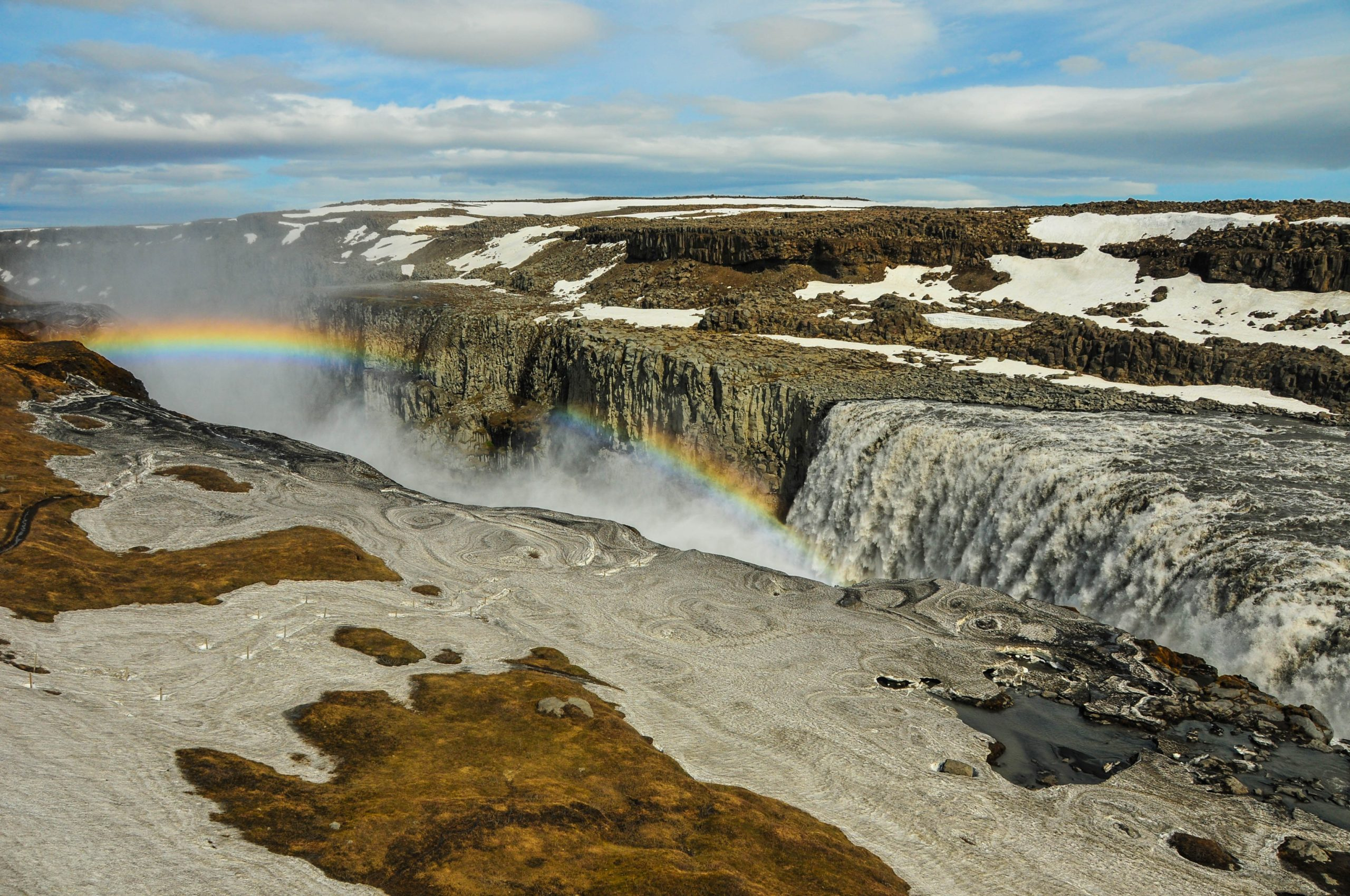 Dettifoss waterfall in northern Iceland with a rainbow across the falls
