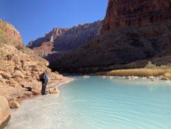 Hiker stnading next to turquoise Little Colorado River on Hayduke