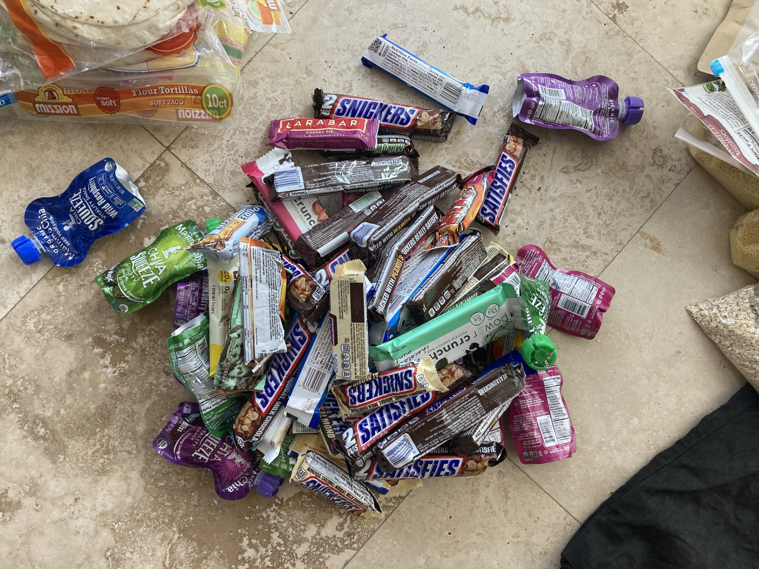 Big pile of bars and candy for food caching along the Hayduke Trail