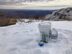 A bucket of food, sparkling water at a cache before going into the Grand Canyon.