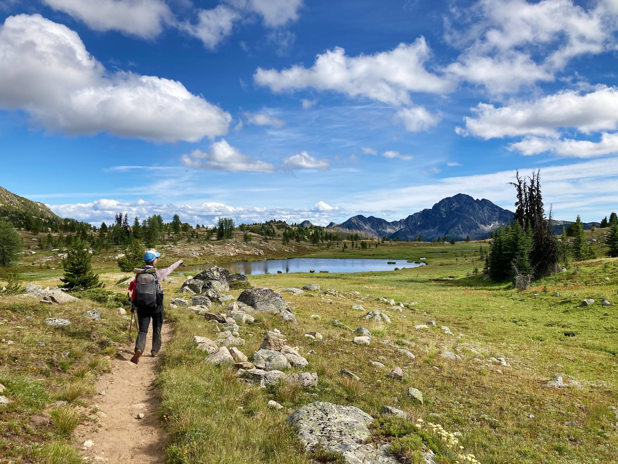Number six top photo. Hiker walking past lake with big mountain view in the distance.