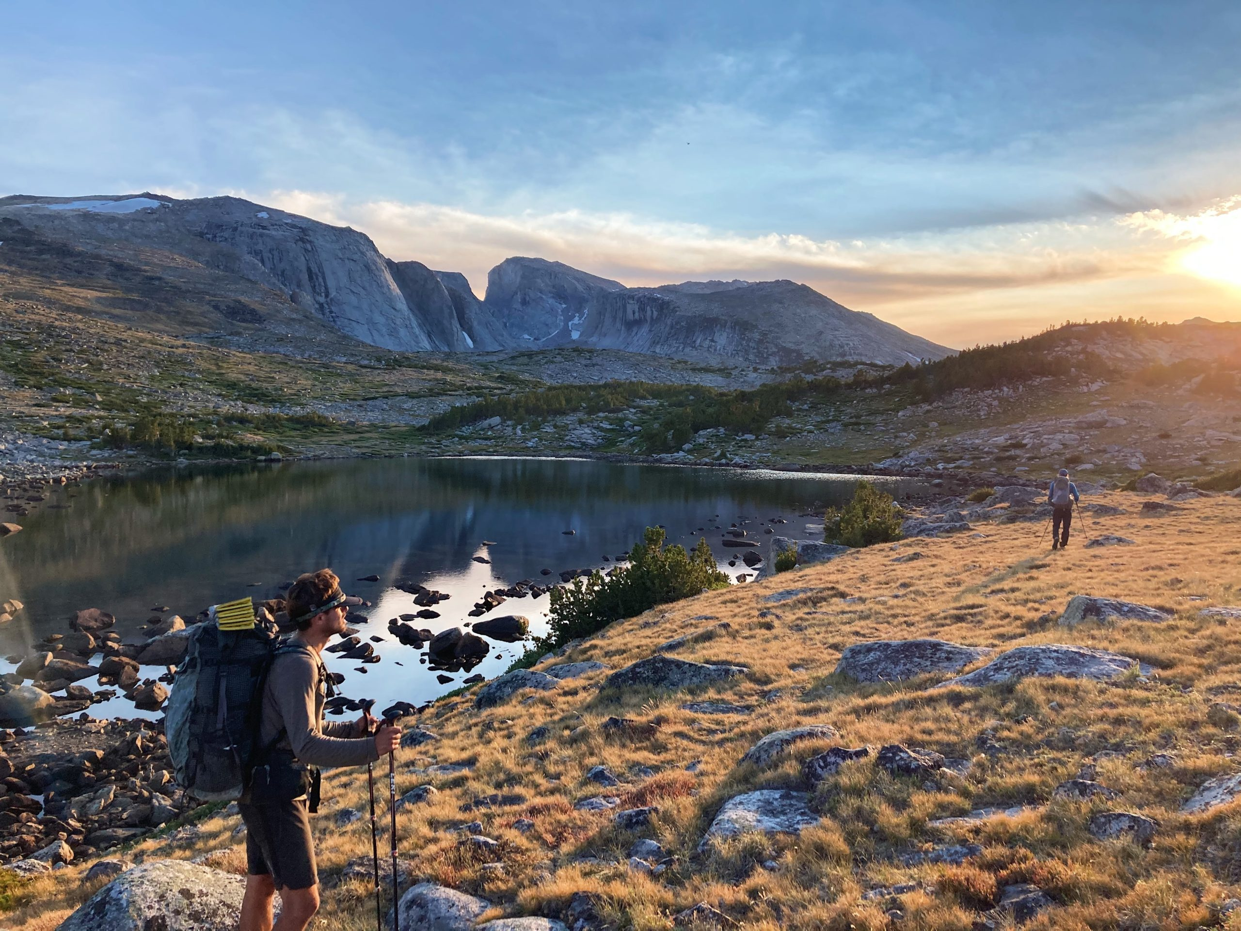 Number Five top photo. Hiker with lake reflection during a mountain sunset.