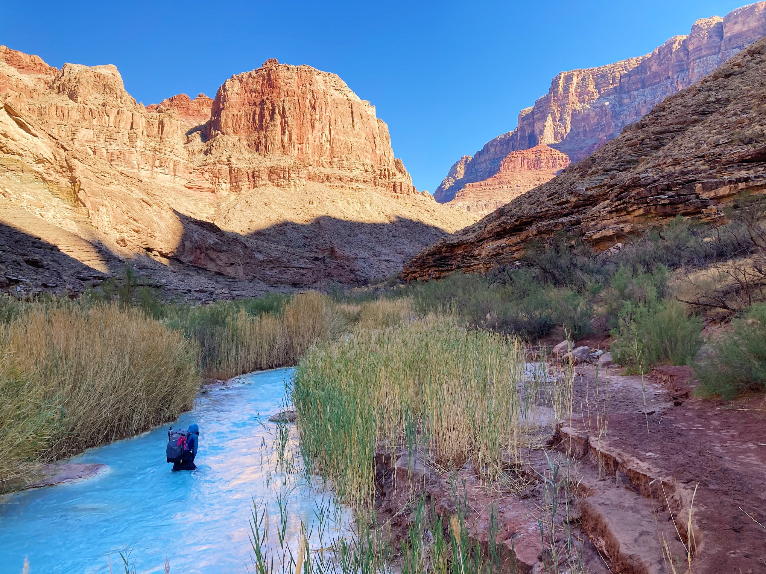 Number one top photo of 2020 hiking season. Hiker wading through Little Colorado River turquoise waters.