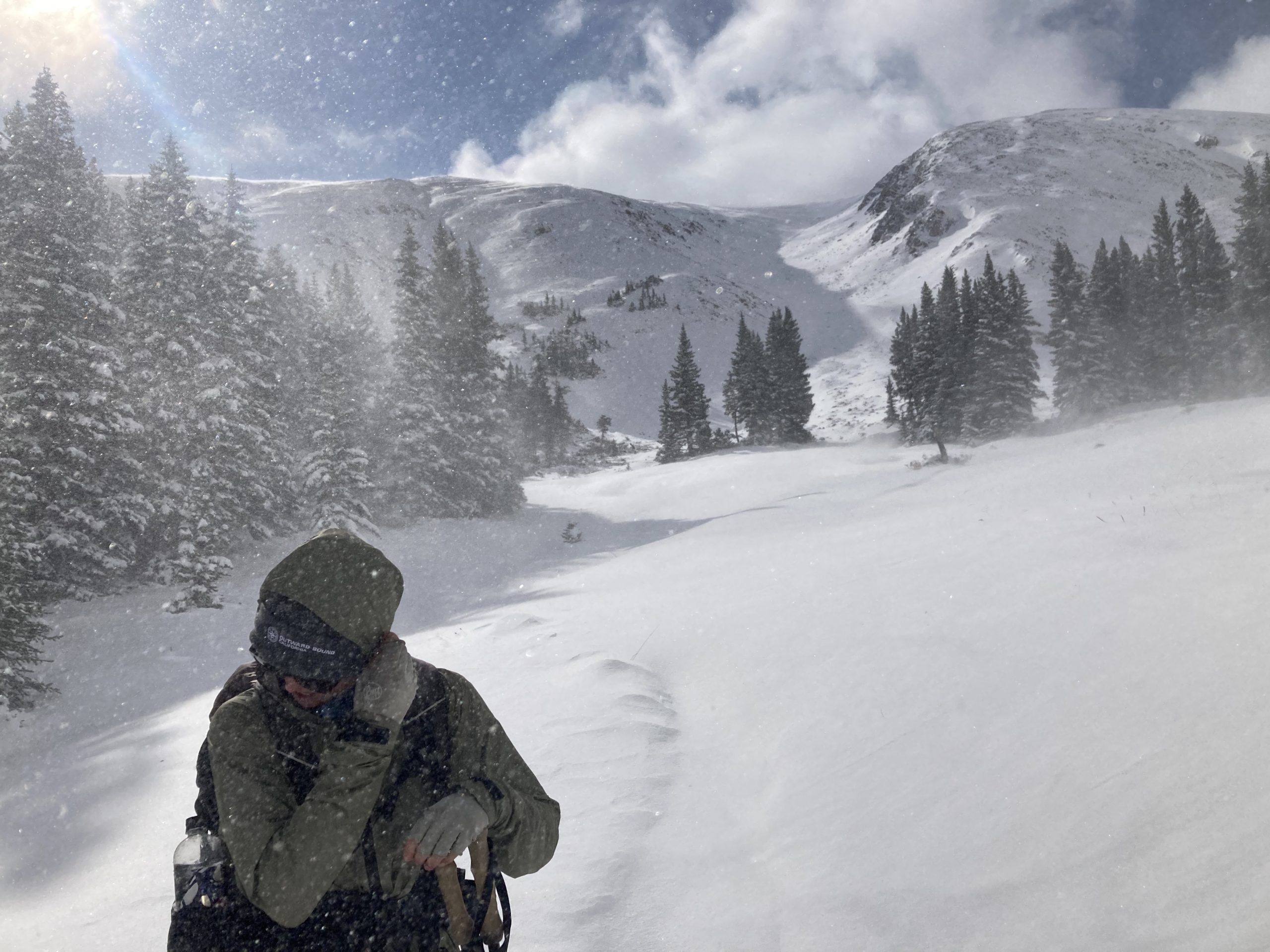 Hiker shielding their face as snow comes whipping up on Colorado Trail