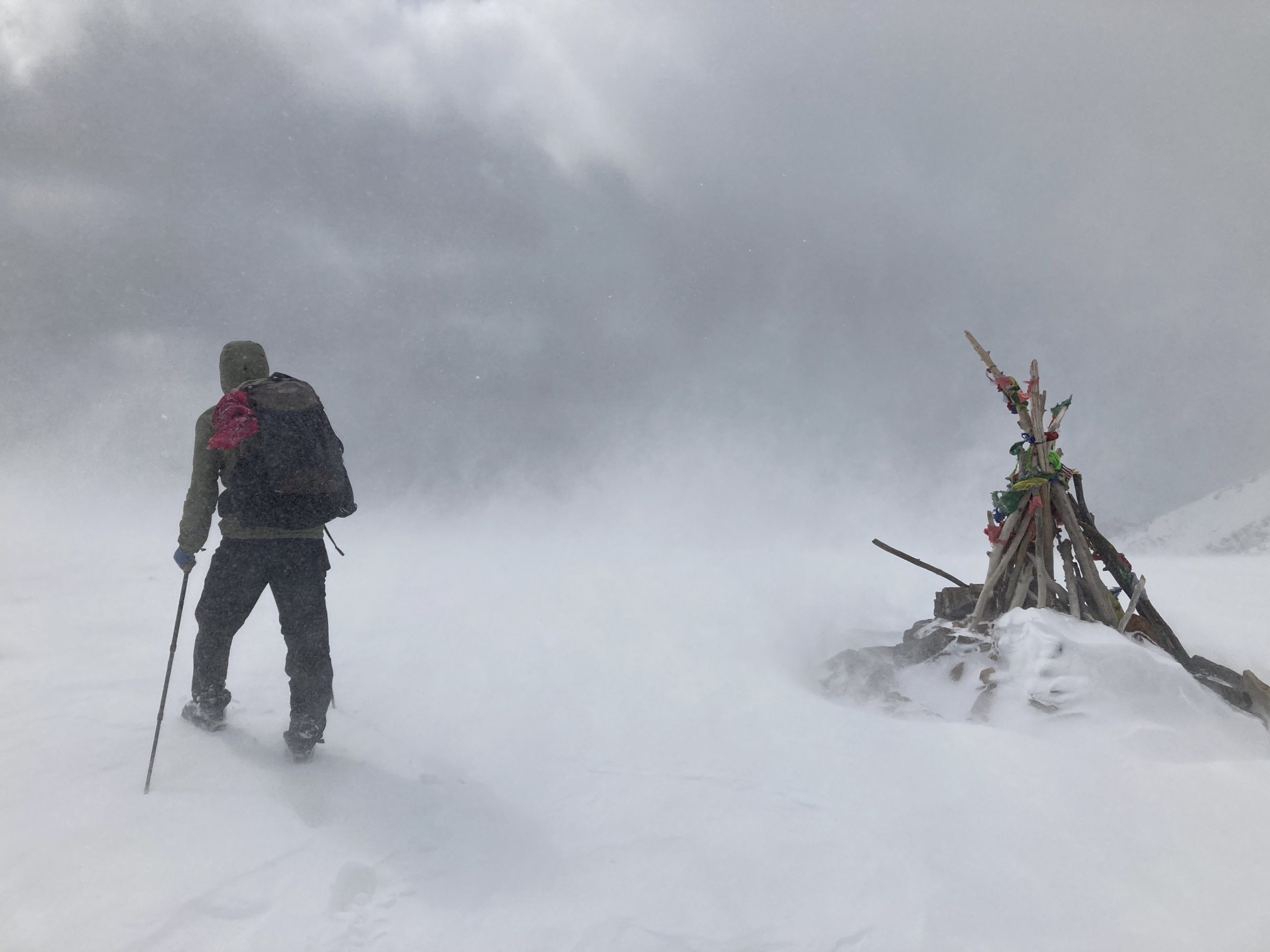 Person hiking in windy snowstorm on top of pass on Colorado Trail in 2020