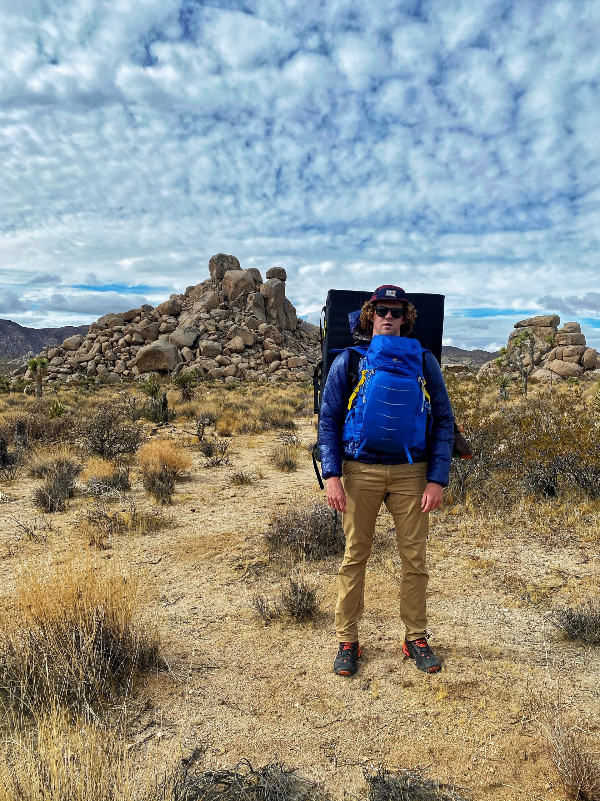 Standing with a crash pad on my back and boulder formations in the background.