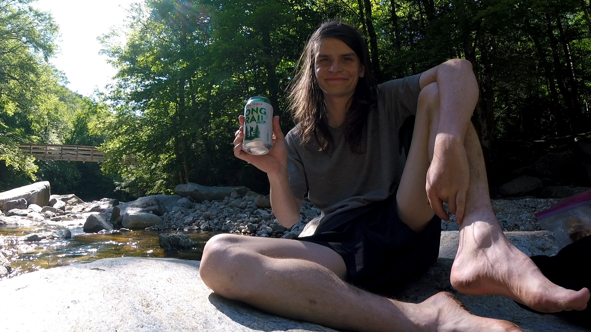 Sitting on a rock holding a can of Long Trail Ale