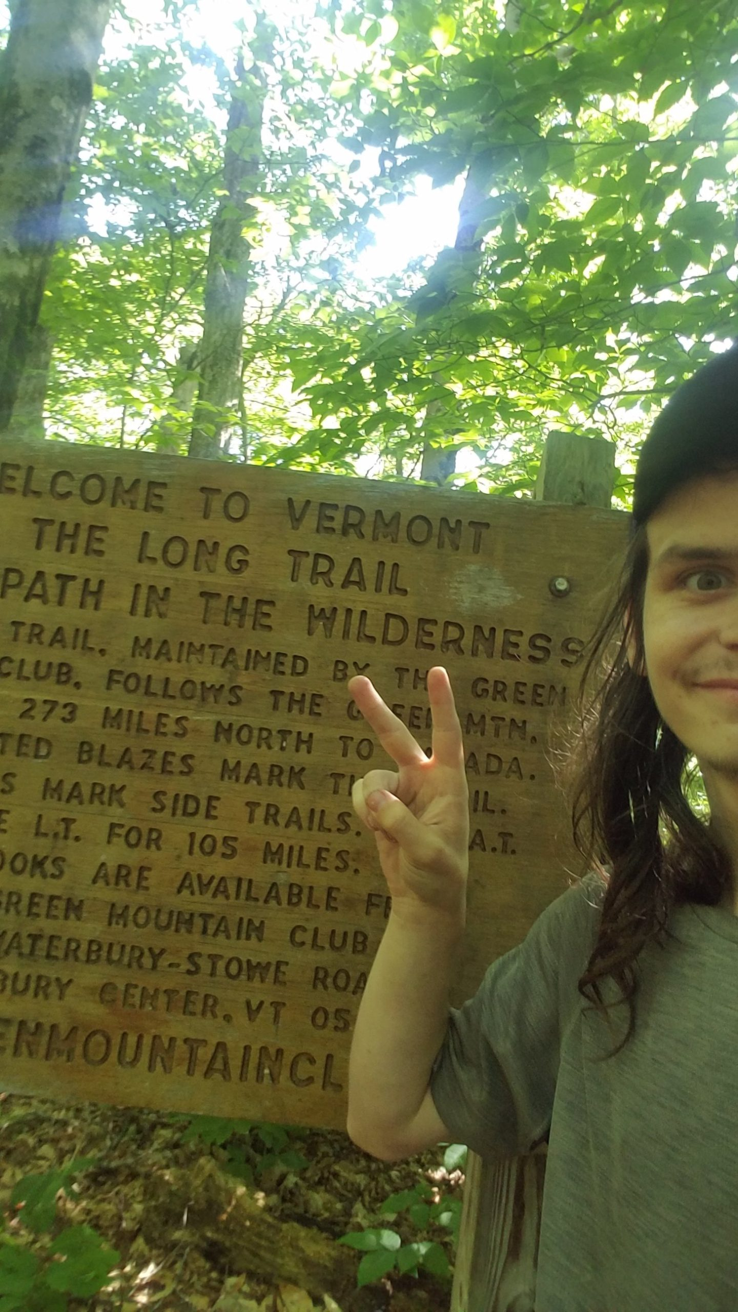 I stand at the Vermont border with a sign indicating the start of the Long Trail ehind me