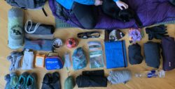woman sitting on sleeping bag with hiking gear arranged around her
