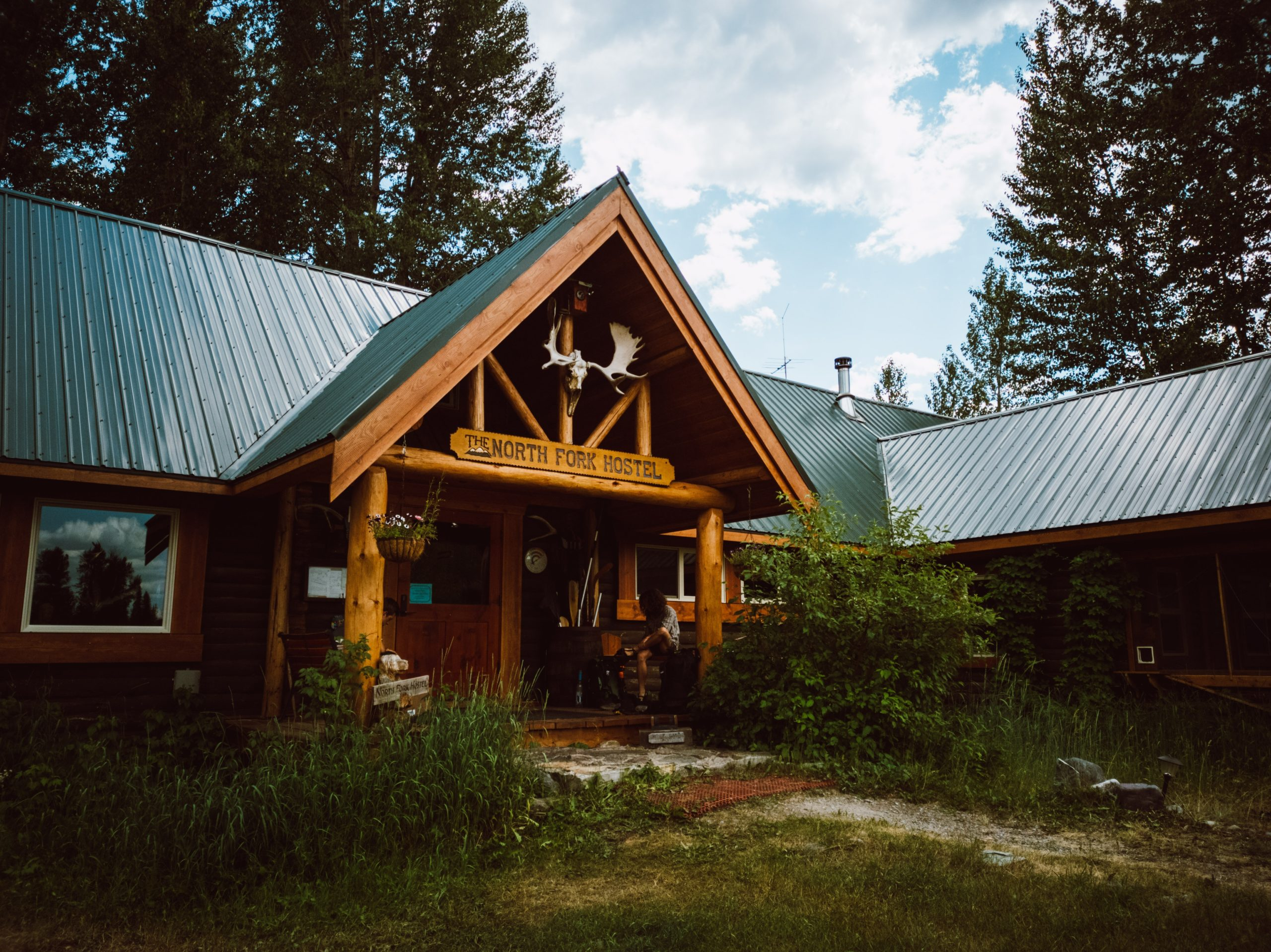 A picture of the North Fork Hostel. It has ana-frame porch with a green metal roof and moose antlers attached to the roof of the porch.