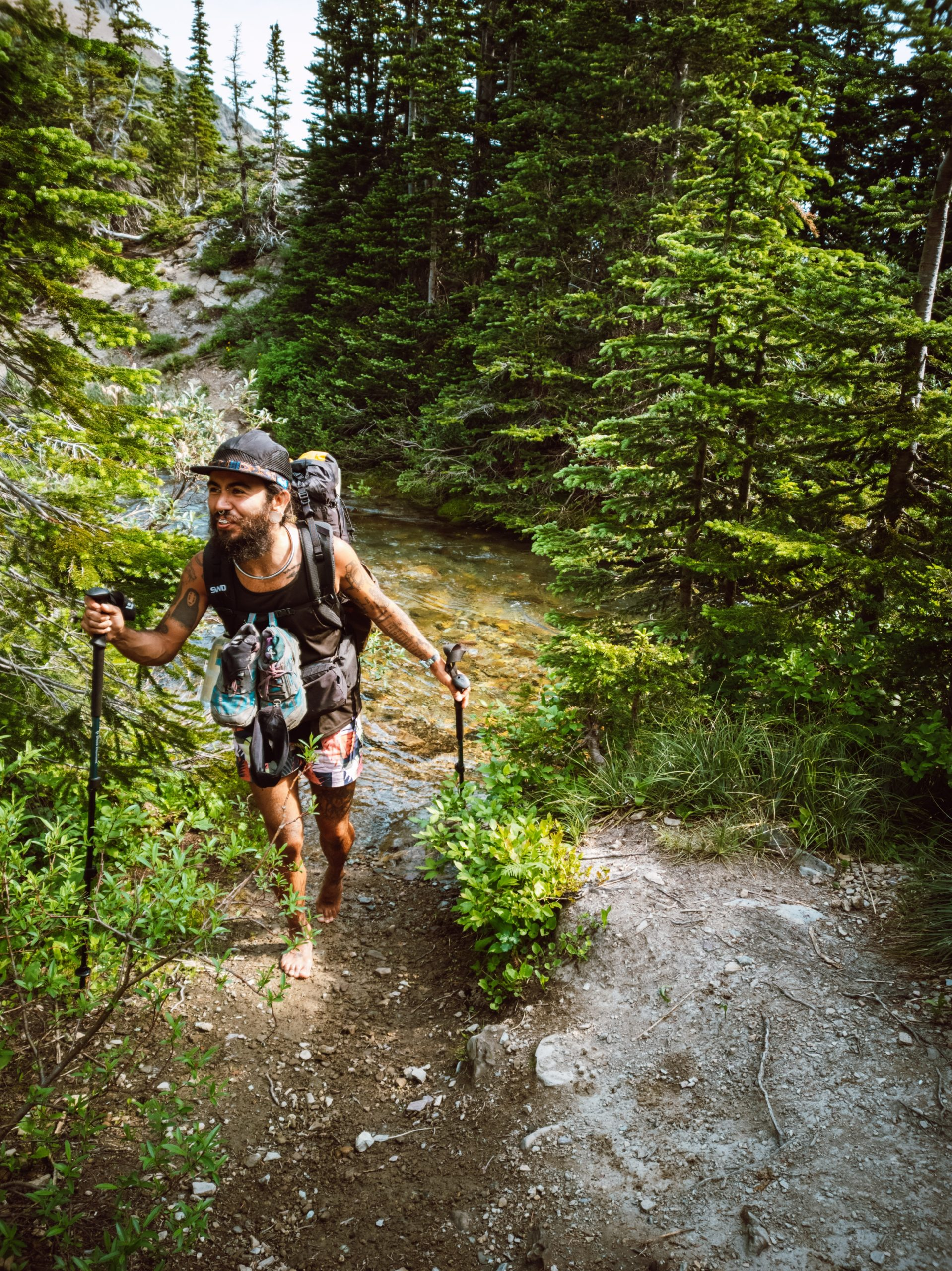 Flower the hiker is facing the camera in the midst of laughing, holding their trekking poles. Their shoes are tethered to their chest strap as they are walking barefoot in front of a stream.
