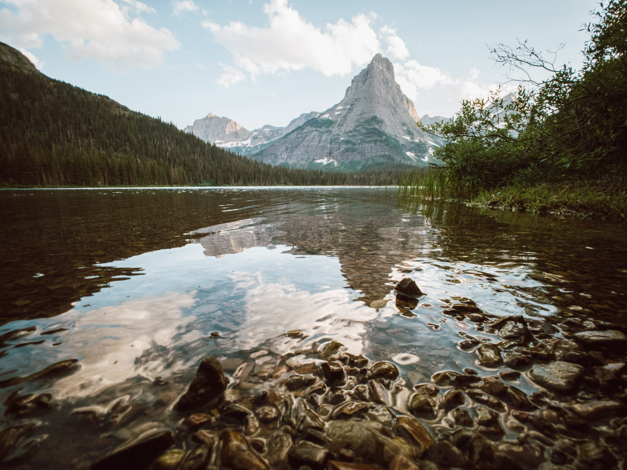 A lake shimmers with the reflection of a pointy mountain peak. There are trees lining the lake and pebbles glistening in the foreground